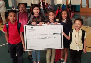 Gifford Youth Achievement Center kids posing with $50,000 grant check
