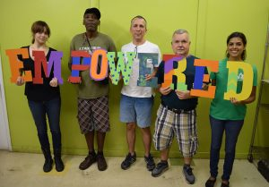 "United Against Poverty volunteers and clients holding cardboard letters that spell ""EMPOWERED"""