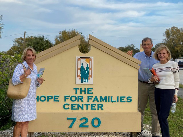Hope for Families Center Brenda Kelsey, Chuck Lyon and Elissa Holmes posing next to organization sign with logo