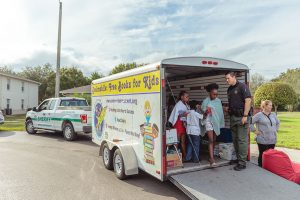 Leaning Alliance bookmobile with kids and sheriff