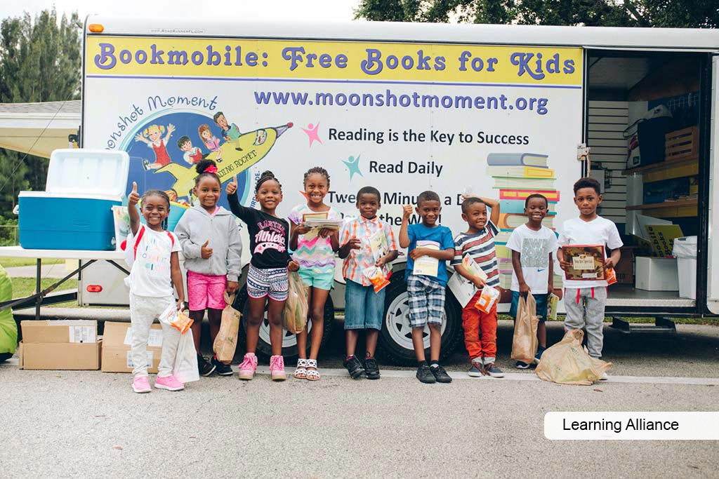 Learning Alliance bookmobile and kids posing with books