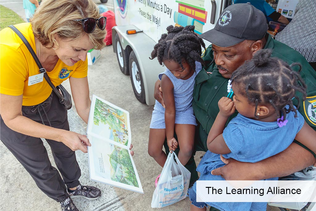 The LEarning Alliance bookmobile woman reading book to kids with father